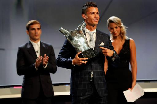 Real Madrid's Portuguese forward Cristiano Ronaldo (C) poses with his trophy of Best Men's player in Europe next to Atletico Madrid's French forward Antoine Griezmann (L) at the end of the UEFA Champions League Group stage draw ceremony, on August 25, 2016 in Monaco. / AFP PHOTO / Valery HACHEVALERY HACHE/AFP/Getty Images