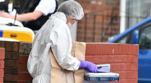 Police and forensics at the scene after a stabbing in west Belfast.