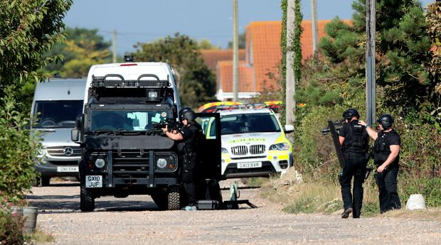 Armed police at the scene on Harbour Road, Pagham, West Sussex, where they are in a stand-off with a 72-year-old man who is thought to have a gun. PA