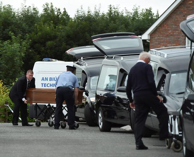 Coffins are taken to hearses at the scene in Oakdene, Barconey, Ballyjamesduff in Cavan, where a family of five were found dead in their countryside home. PA