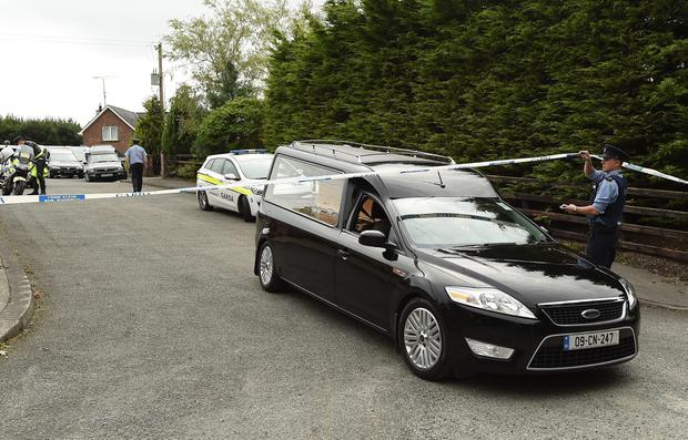 A Garda technical officer lifts tape as a hearse leaves the scene at Oakdene, Barconey, Ballyjamesduff in Cavan, where a family of five were found dead in their countryside home. PA