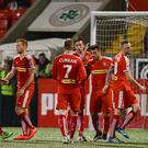 Centre of attention: David McDaid is mobbed by Cliftonville team-mates after completing his hat-trick from the penalty spot at Solitude
