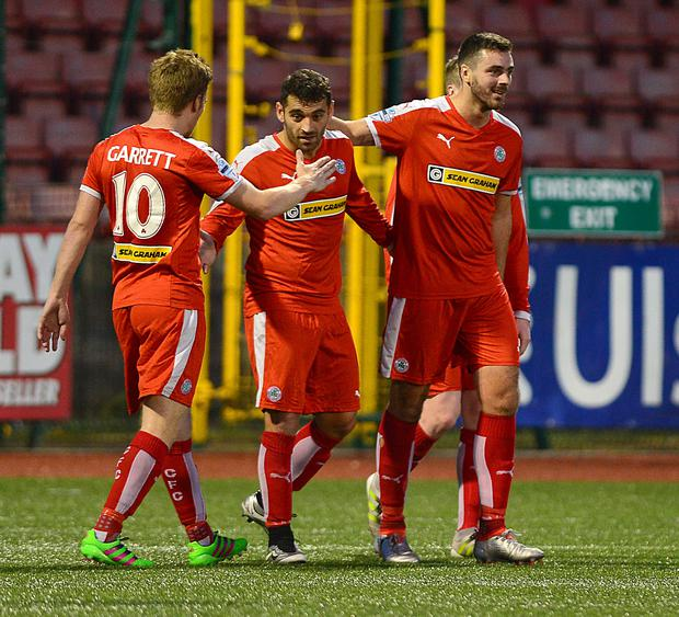 Three and easy: David McDaid takes the plaudits from team-mates after netting a hat-trick in Cliftonville's 11-1 triumph over Lisburn Distillery