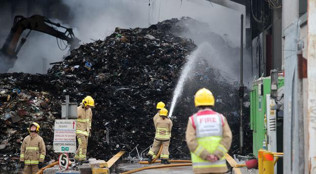 Firefighters dampen the smouldering remains at the Wastebeater plant in Kennedy Way