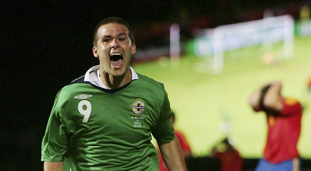 Treble yell: David Healy shows his delight after sealing his hat-trick and Northern Ireland's remarkable 3-2 win over Spain exactly 10 years ago