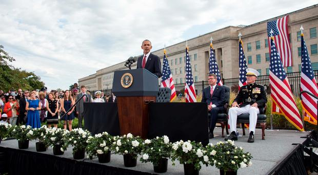 US President Barack Obama speaks during a ceremony commemorating the September 11, 2001 attacks, with Defense Secretary Ashton Carter (2nd R) and Joint Chiefs of Staff Gen. Joseph Dunford (R) at the Pentagon in Washington, DC, on September 11, 2016. / AFP PHOTO / NICHOLAS KAMMNICHOLAS KAMM/AFP/Getty Images
