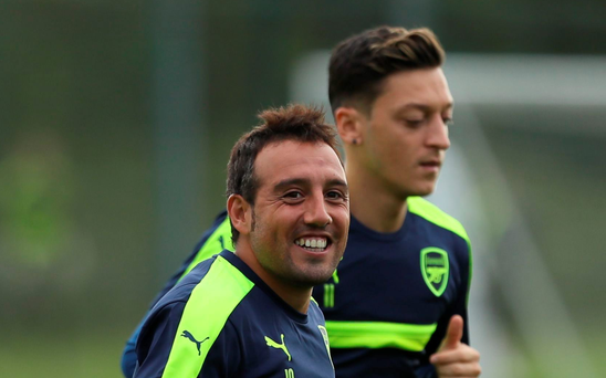 On the run: Arsenal's Santi Cazorla and Mesut Ozil train in London ahead of the Champions League clash with PSG