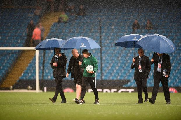 Match officials inspect the pitch as heavy rain continues to pour ahead of the UEFA Champions League group C football match between Manchester City and Borussia Monchengladbach at the Etihad stadium in Manchester, northwest England, on September 13, 2016. AFP/Getty Images