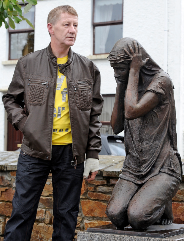 Mark Aiken, whose sister Kathryn was one of nine people killed in the Claudy bombings, stands beside the village's memorial to the victims