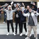 The first group of customers including Bishoy Behman, left, and Marcus Barsoum, right, hold up their purchases at the Apple store in Sydney, Australia, Friday, Sept. 16, 2016. The latest iPhone was released in the country on Friday. (AP Photo/Rob Griffith)