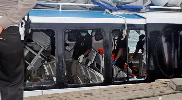 Police investigators examine the Gili Cat 2 boat following an explosion while it was enroute to nearby island of Lombok, at Padangbai Port in Karangasem, Bali, Indonesia, Thursday, Sept. 15, 2016. (AP Photo)