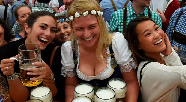 Visitors enjoy the atmosphere and take selfies as a waitress serves beer mugs during the opening of the Oktoberfest beer festival in a festival tent at the Theresienwiese in Munich, southern Germany, on September 17, 2016.