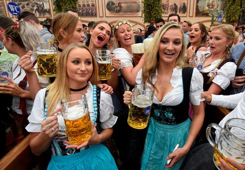 Visitors react as a waitress carries the beer mugs, during the opening of the Oktoberfest beer festival in a festival tent at the Theresienwiese in Munich, southern Germany, on September 17, 2016. The World's largest beer festival Oktoberfest will run until October 3, 2016. / AFP PHOTO / CHRISTOF STACHECHRISTOF STACHE/AFP/Getty Images