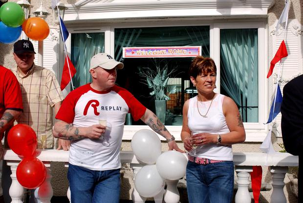 Loyalist paramilitary leader Johnny Adair pictured with his wife Gina outside their Shankill Road home after he was released from prison