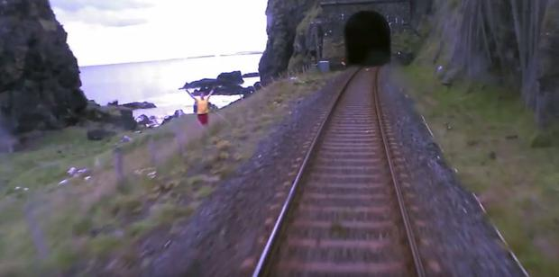 A man is seen trying to flag the train down.