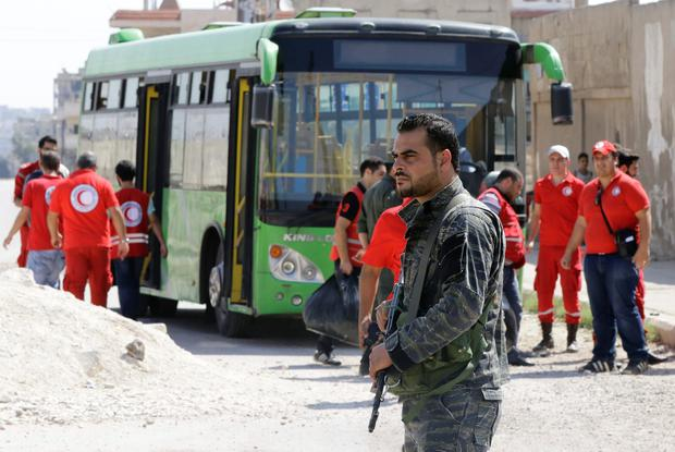 A Syrian soldier stands guard as Red Crescent members wait for opposition fighters and their families to change buses at a Syrian army checkpoint on the edge of the rebel-held Waer neighbourhood in the central city of Homs during an evacuation operation on September 22, 2016. AFP/Getty Images