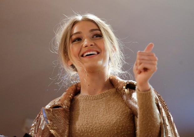 Model Gigi Hadid, hosted by Max Mara, salutes fans from the flagship store during the women's Spring-Summer 2017 fashion event, in Milan, Italy, Wednesday, Sept. 21, 2016. (AP Photo/Luca Bruno).