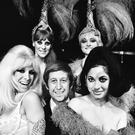 21st July 1967: Club owner Paul Raymond and four of his revue dancers, who are on their way to Aden to entertain the troops. The dancers are Carole Ryva, Jean Crabtree, Lady Flan and Sandra Bunting. (Photo by C. Maher/Express/Getty Images)