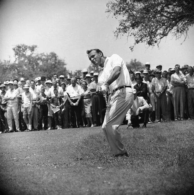 File-This April 29, 1962, file photo shows Arnold Palmer, lifting an iron shot from No. 5 fairway in the final round of the Texas Open in San Antonio. Palmer, who made golf popular for the masses with his hard-charging style, incomparable charisma and a personal touch that made him known throughout the golf world as