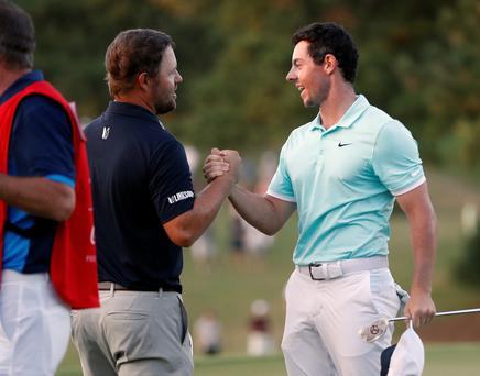 Rory McIlroy, right, shakes hands with Ryan Moore after winning at the Tour Championship golf tournament and the FedEX Cup at East Lake Golf Club, Sunday, Sept. 25, 2016, in Atlanta. (AP Photo/John Bazemore)