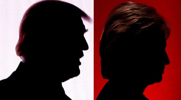 Silhouettes of Republican presidential nominee Donald Trump(R)July 18, 2016 and Democratic presidential nominee Hillary Clinton on February 4, 2016. AFP/Getty Images