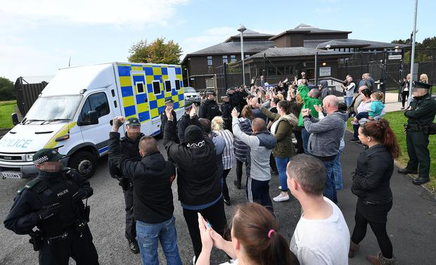 Police form a security line as family, friends and supporters cheer at a police cell van, carrying four remanded men, leaving Craigavon Courthouse today