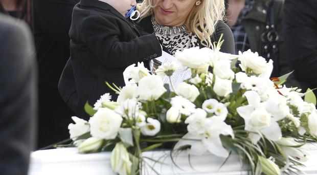 Mum Lisa Carlisle holds Logan as he touches the coffin