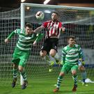 On the defensive: Stephen Heaney clears under pressure from Derry's Rory Patterson
