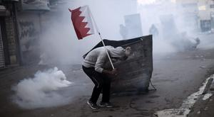 A Bahraini protester takes cover during clashes with police