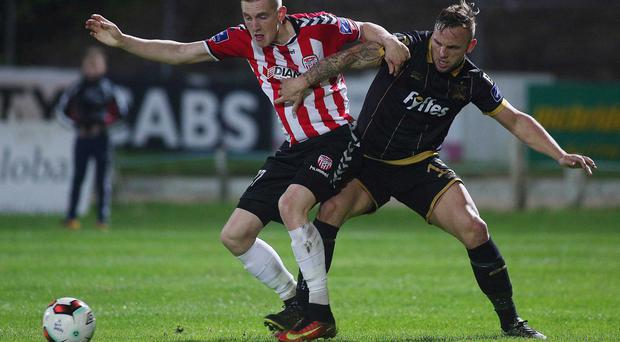 Tight tussle: Derry's Ronan Curtis and Patrick Barrett of Dundalk battle for the ball