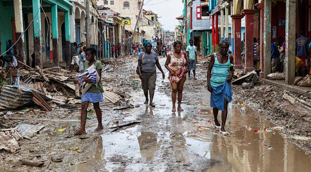TOPSHOT - Picture taken by the UN Mission in Haiti (MINUSTAH) in the town of Jeremie, Haiti on Thursday October 6, 2016 showing people walking down a flooded street. The city lies on the western tip of Haiti and suffered the full force of the category 4 storm, leaving tens of thousands stranded. Hurricane Matthew passed over Haiti on Tuesday October 4, 2016, with heavy rains and winds. While the capital Port au Prince was mostly spared from the full strength of the class 4 hurricane, the western cities of Les Cayes and Jeremie received the full force sustaining wind and water damage across wide areas. / AFP PHOTO / UN/MINUSTAH / Logan Abassi / RESTRICTED TO EDITORIAL USE - MANDATORY CREDIT