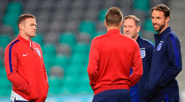 Miles away: Wayne Rooney (left) during a walkabout on the pitch with caretaker manager Gareth Southgate (right) and Jamie Vardy last night in Ljubliana