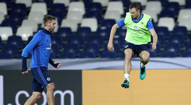 Leap of faith: Northern Ireland central defenders Gareth McAuley (left) and Jonny Evans at last night's training session at the HDI Arena in Hannover