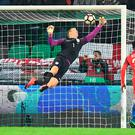 Wonder save: Joe Hart pushes the ball onto the crossbar and then claws it away to prevent a Slovenia goal in Ljubljana