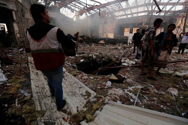 People inspect the aftermath of a Saudi-led coalition airstrike in Sanaa, Yemen, Saturday, Oct. 8, 2016. Yemeni security and medical officials say at least 45 people have been killed in a Saudi-led coalition airstrike that targeted a funeral hall in the capital, Sanaa. The officials say at least another 100 have been wounded in the Saturday strike. (AP Photo/Osamah Abdulrhman)