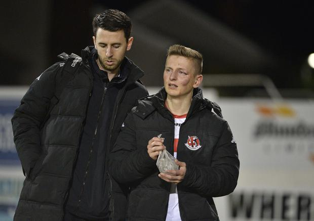 Pain game: Crusaders winger Ross Holden walks around the Shamrock Park pitch after suffering a horrific head injury against Portadown in the League Cup