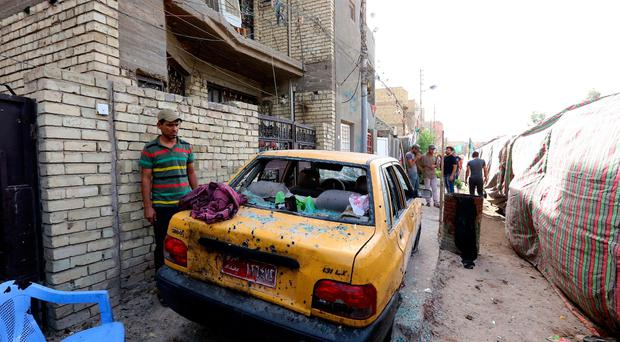 An Iraqi inspects a damaged car at the site of a suicide bombing that targeted Shiite Muslims on October 15, 2016 in the Shaab area of the Iraqi capital Baghdad. AFP/Getty Images