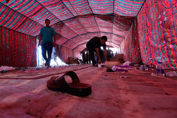 Iraqis clean a tent at the site of a suicide bombing that targeted Shiite Muslims on October 15, 2016 in the Shaab area of the Iraqi capital Baghdad. AFP/Getty Images