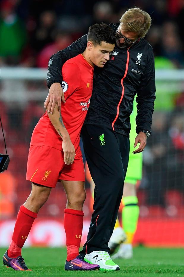 Liverpool's German manager Jurgen Klopp embraces Liverpool's Brazilian midfielder Philippe Coutinho after the English Premier League football match between Liverpool and Manchester United at Anfield in Liverpool, north west England on October 17, 2016. AFP/Getty Images