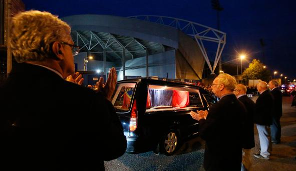 Crowds line the street as a hearse carrying the coffin of Shannon and Munster Rugby club's head coach Anthony Foley passes Thomond Park stadium in Limerick. PA