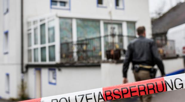Police investigators stand outside the house where a 49-year-old