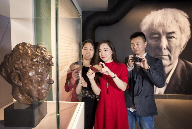 Chinese bloggers Min Lin Siew, Yan Ma, and Pu Zang are pictured taking a selfie in front of Seamus Heaney's portrait. Picture by Brian Morrison.
