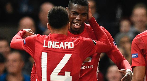 Manchester United's French midfielder Paul Pogba (R) and Manchester United's English midfielder Jesse Lingard (L) celebrate after Pogba scored their third goal during the UEFA Europa League group A football match between Manchester United and Fenerbahce at Old Trafford in Manchester, north west England, on October 20, 2016. / AFP PHOTO / OLI SCARFFOLI SCARFF/AFP/Getty Images