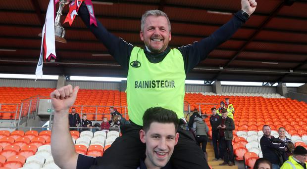 On a high: Slaughtneil manager Mickey McShane is lifted shoulder high by Cormac Donnelly after the historic win over Loughgiel at the Athletic Grounds yesterday