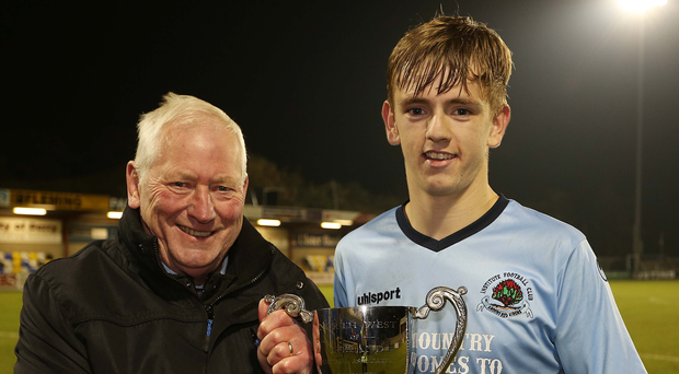 Champions: Billy Smallwoods presenting the NW Senior Cup trophy to Institute captain Ciaran Harkin