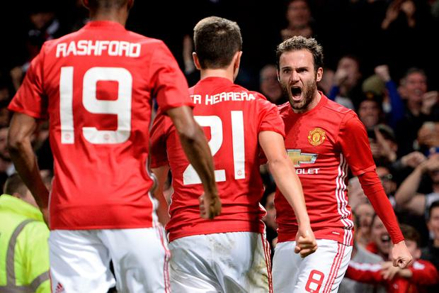 Manchester United's Spanish midfielder Juan Mata (R) celebrates with teammates after scoring the opening goal of the EFL (English Football League) Cup fourth round match between Manchester United and Manchester City at Old Trafford in Manchester, north west England on October 26, 2016.AFP/Getty Images