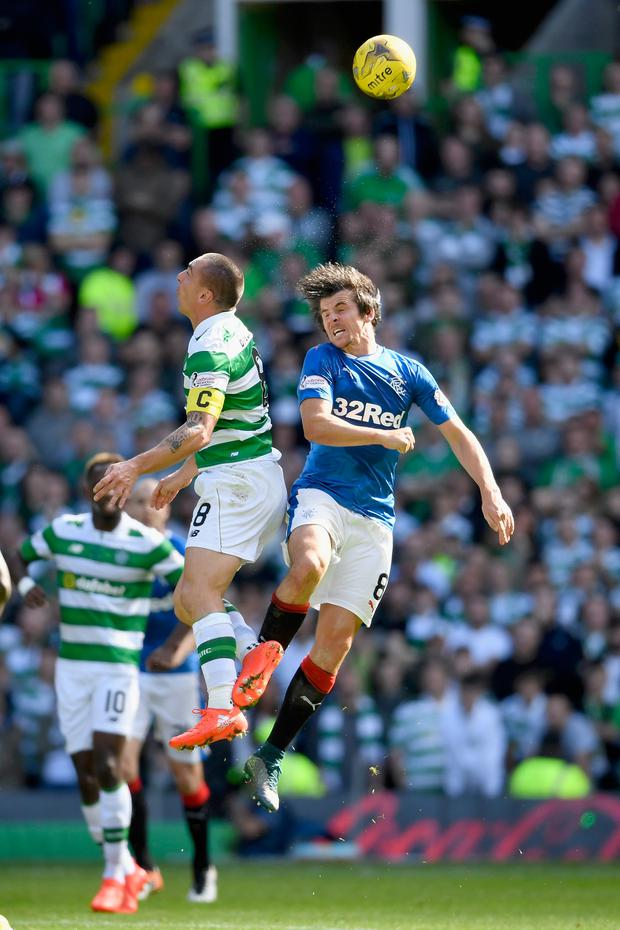 High jump: Joey Barton (right) battling with Scott Brown in the Old Firm game which sparked his Ibrox suspension