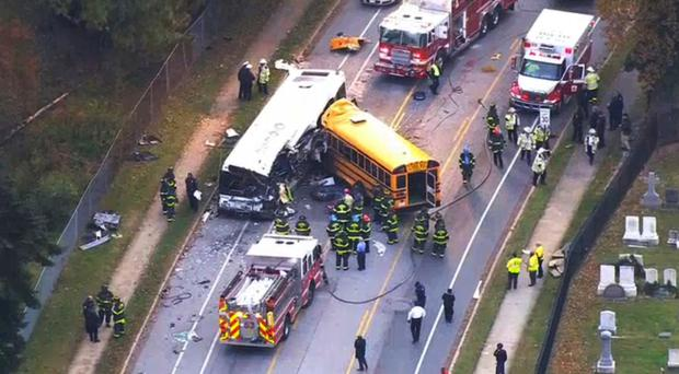 Emergency personnel work at the scene of a fatal school bus and a commuter bus crash in Baltimore