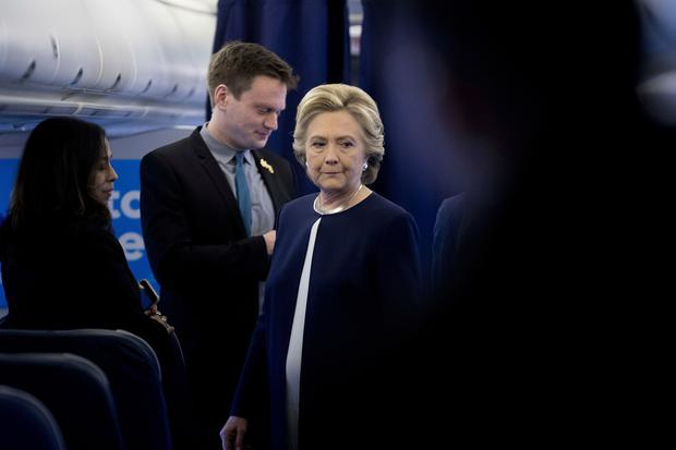 Democratic presidential candidate Hillary Clinton, accompanied by aides Teddy Goff, second from left, and Mia Harris, left, aboard her campaign plane at Westchester County Airport in White Plains, N.Y., Friday, Nov. 4, 2016, before traveling to Pittsburgh for a rally. (AP Photo/Andrew Harnik)
