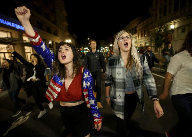 Madeline Lopes, left, and Cassidy Irwin, both of Oakland, march with other protesters in downtown Oakland, Calif., early Wednesday, Nov. 9, 2016. President-elect Donald TrumpÄôs victory set off multiple protests. (Jane Tyska/Bay Area News Group via AP)
